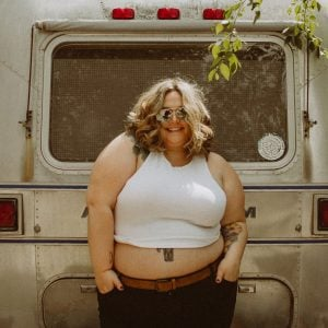 Plus size woman Corissa Enneking in front of vintage silver truck. she is smiling with her hands in her pockets. wearing a white tank top crop top, aviator style sunglasses, and blue jeans with skinny brown belt. hair is parted down the middle, curly, and blonde.